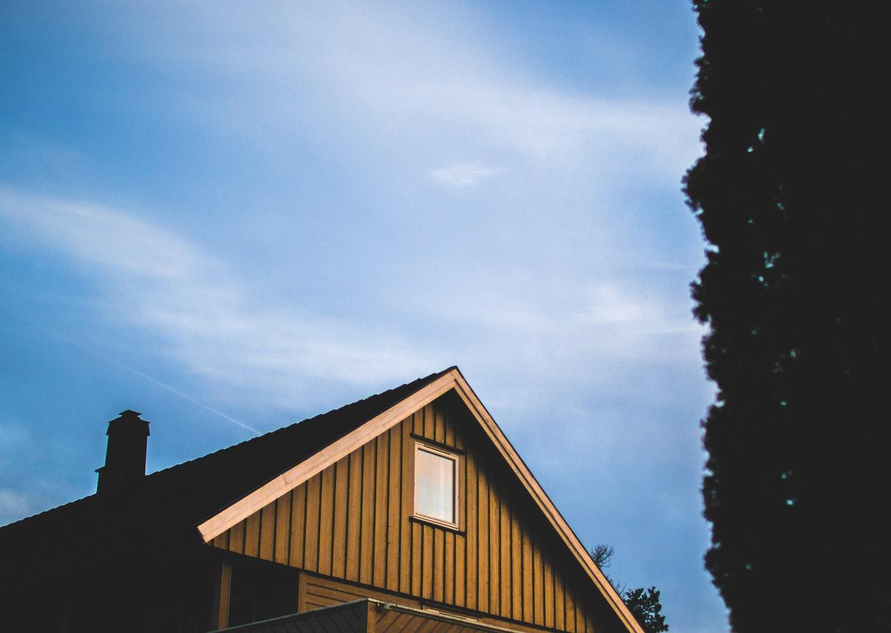Blå himmel skinner over brunt træhus